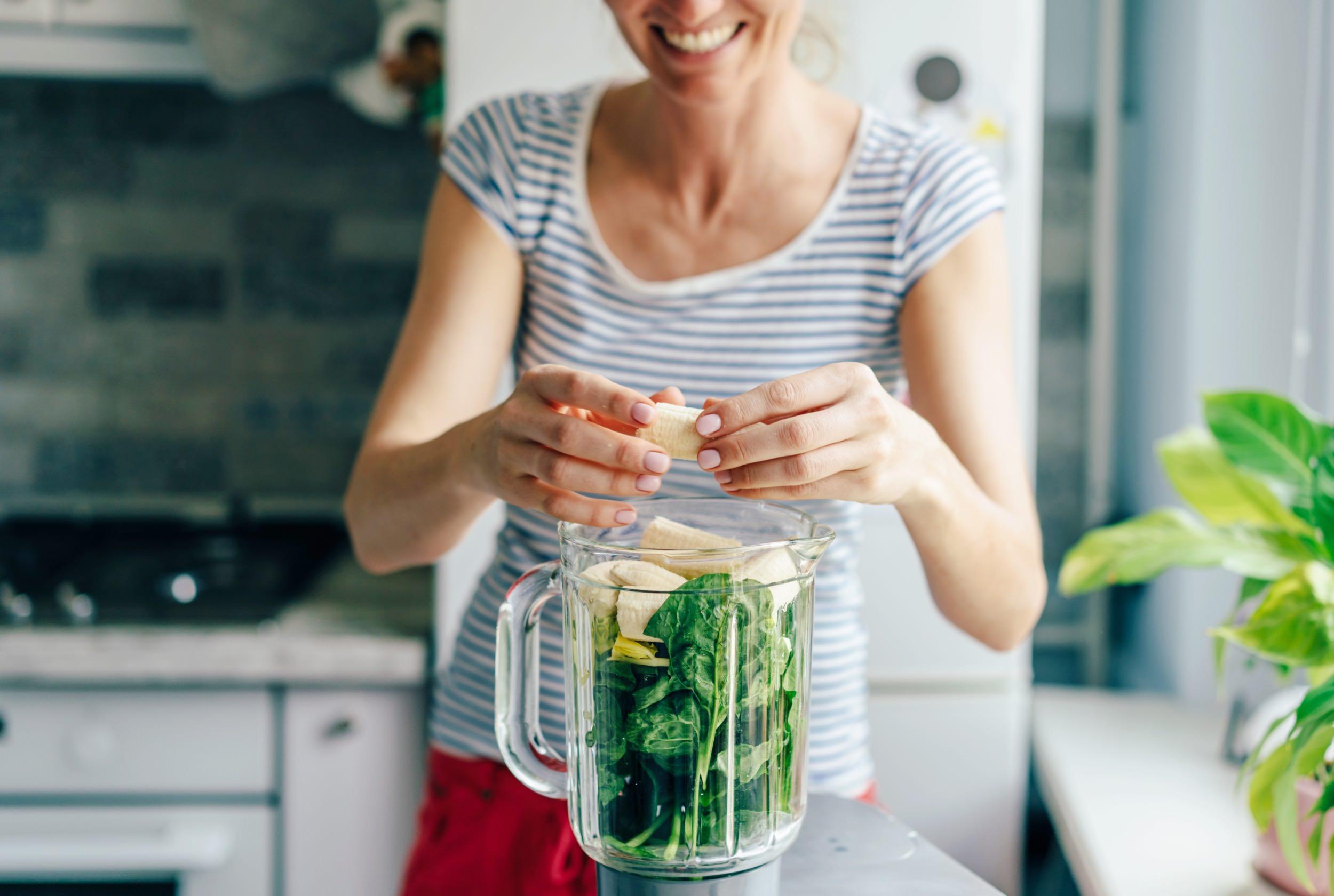 Woman prepares greens in a blender